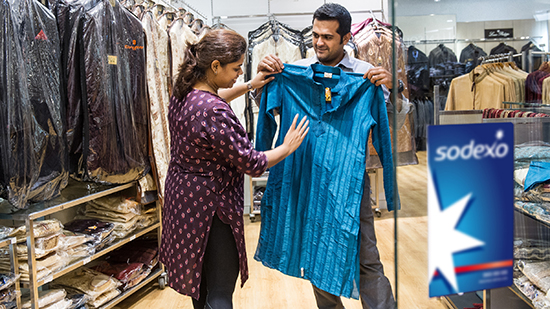 A woman holding up an item of clothing against a customer
