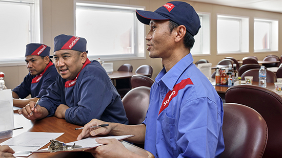 Three Sodexo employees sitting at a table and listening