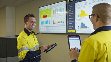 Two facilities management employees talking, holding a tablet with screens showing data in the background