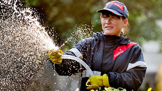 Women in Sodexo uniform watering flowers