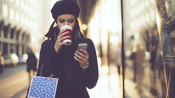 Female adult reading her mobile phone and drinking a coffee whilst walking and holding a shopping bag